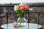 spring flower bouquet in glass jug on table