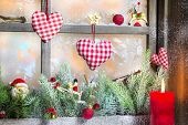 Christmas decoration with red candle on window sill