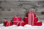 Stack of red Christmas gift boxes with snow on grey wooden background for a greeting card or shopping, coupon..