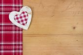 Christmas : Red and white fabric with checked heart on wooden background