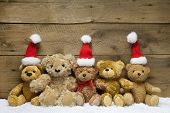 Five teddy bears with Christmas hats on wooden background