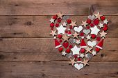 Christmas heart on a wooden background with different decoration in red and white