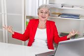 Laughing businesswoman in red sitting at desk with raised arms