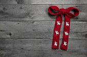 Red knitted bow with deers on wooden background