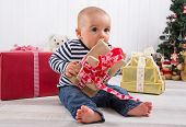 First Christmas: barefoot baby unwrapping a red present