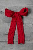 Red knitted bow for a present on grey wooden background - greeting card for christmas or birthday