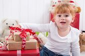 picture of strawberry blonde  - Young girl with Christmas presents and teddy bears in background  - JPG