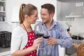 Couple celebrate love - cooking together in the kitchen and have fun - drinking red wine