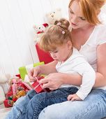 Together: daughter sitting on mother's lap with presents on birthday or christmas
