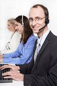 Telesales or helpdesk team - helpful man with headset smiling at camera
