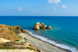 stock photo of saracen  - The cozy beach next to the Aphrodite birthplace with the Saracen rock in the sea Paphos Cyprus - JPG