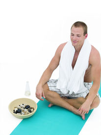 foto of yoga mat  - Handsome man relaxing and sitting on a green mat meditating - JPG