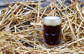 pic of stein  - Horizontal image of a glass stein filled with dark draft stout beer on rustic wood and straw - JPG