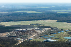 foto of polution  - Aerial view of a gigantic hill of garbage contrasted with a green unspoiled landscape around near Moscow Russia - JPG