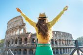 Young Woman Rejoicing In Front Of Colosseum In Rome, Italy. Rear