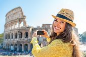 Happy Young Woman Taking Photo Of Colosseum In Rome, Italy