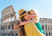 Portrait Of Mother And Baby Girl Hugging In Front Of Colosseum In Rome, Italy