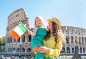 Happy Mother And Baby Girl With Italian Flag In Front Of Colosseum In Rome, Italy