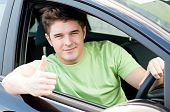 image of driving school  - Handsome male driver sitting in a car and smiling - JPG