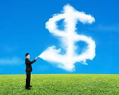 Businessman Spraying Dollar Sign Shape Cloud Paint With Sky Grass