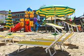 Children's Playground, Beach Chairs And Umbrellas On The Beach  In The Resort Town Bellaria Igea Mar