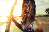 Portrait anf the young lady with surf board on the beach