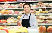 Storekeeper smiling in his grocery store holding a speck