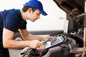 Skilled mechanic using a laptop computer to check a car engine