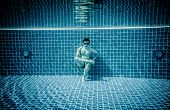Man sitting on the bottom of the swimming pool under water
