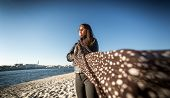 picture of windy  - Portrait of brunette woman in scarf posing on beach at windy day - JPG