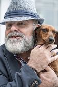 Attractive Old Man With Beard And Hat With Dog Teckel