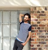 Young Man With Beard Leaning Against Wall Outdoors