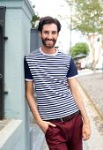Happy Trendy Man In Striped Shirt Leaning Against Wall Outdoors