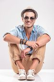 Young casual man sitting on studio background with his knees up, holding his hands together, smiling.