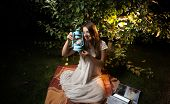 stock photo of night gown  - Beautiful young woman looking at old lantern while sitting at night garden - JPG
