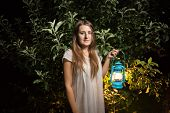 picture of night gown  - Portrait of beautiful brunette woman waling at night garden with vintage lantern - JPG