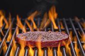 pic of hamburger  - Hamburger patty on a hot flaming grill - JPG