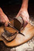 image of fresh slice bread  - Male hands slicing fresh bread on wood table  - JPG