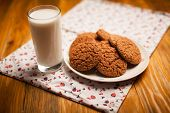 Oatmeal Cookies And Glass Of Milk On Napkin On Table
