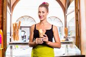 Woman selling ice cream cone in cafe