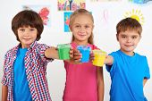 stock photo of health center  - Two smiling little boys and cute girl looking at camera and holding colorful cans with paint. Preschool center for children