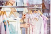 Beautiful young woman choosing new blouse for summer