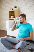 Handsome guy drinking tea or coffee while using modern gadgets at home