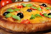 Pizza with cheese and vegetables on wooden board and dark colorful background