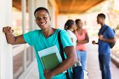 cheerful african college boy with books standing by passage