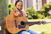 pretty african college girl practicing guitar on campus