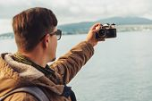 Young Man Takes Photographs Self-portrait On Coast
