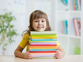 pic of hardcover book  - Happy kid girl with a stack of books at home