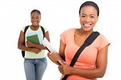 cheerful african american college student holding laptop on white background