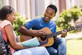 romantic young african college student playing guitar for his girlfriend on campus